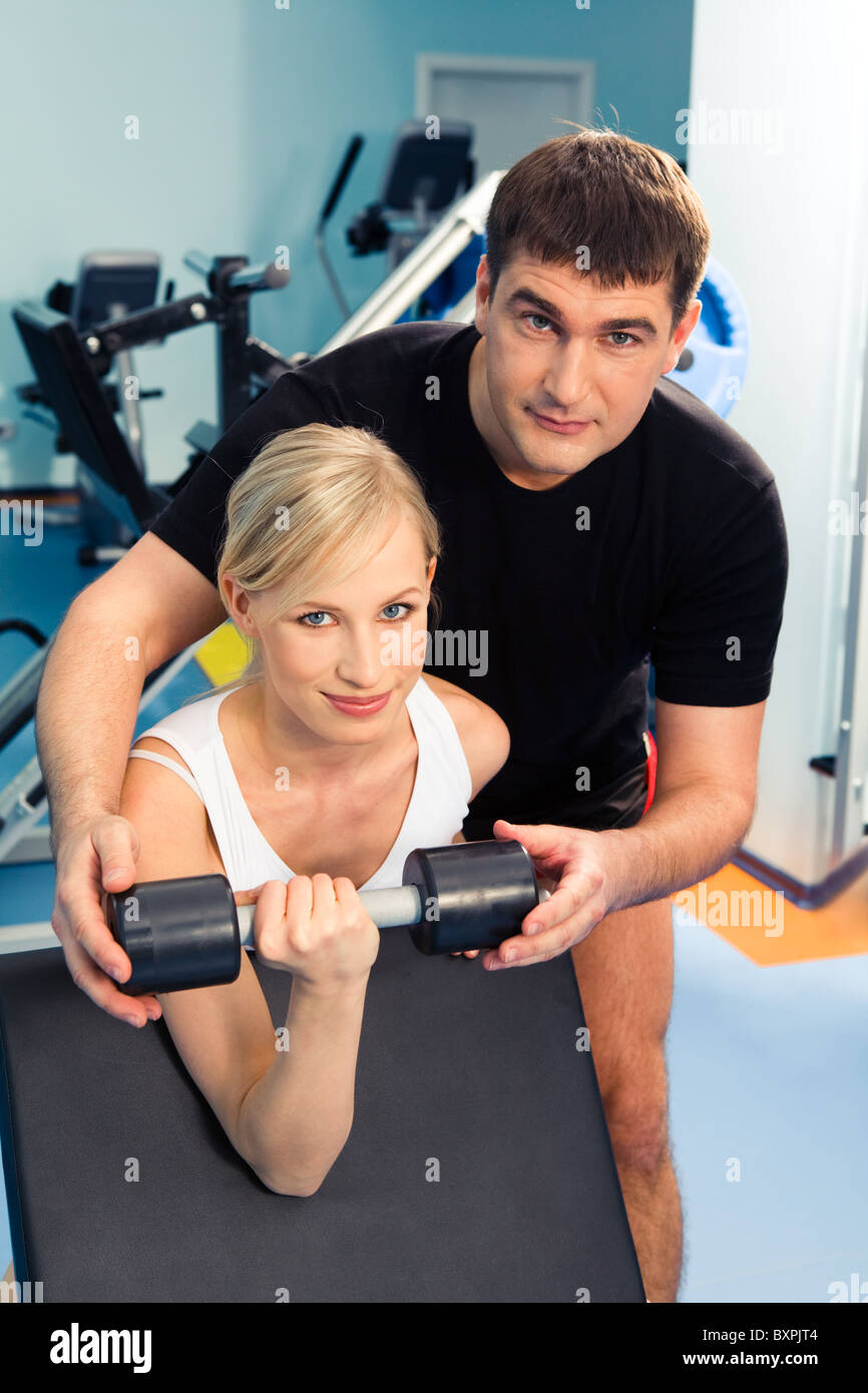 Blonde woman lifting weight with man assisting her in the sport club - Stock Image