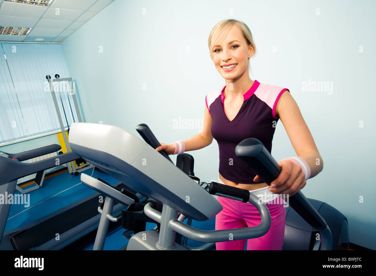 Image of pretty girl in sportwear on the treadmill running - Stock Photo