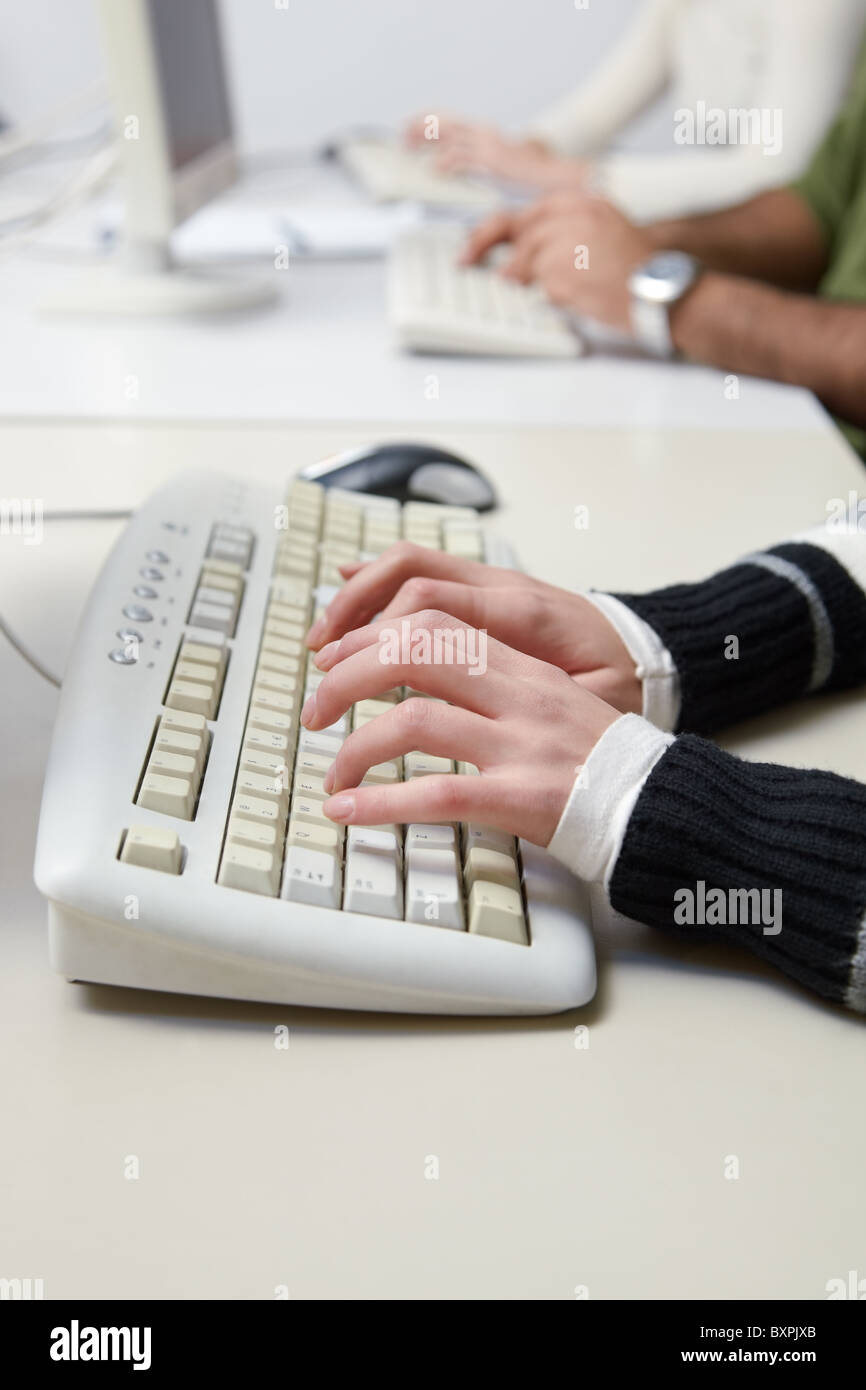 Closeup of caucasian female student typing on keyboard in computer lab. Vertical shape, side view - Stock Image