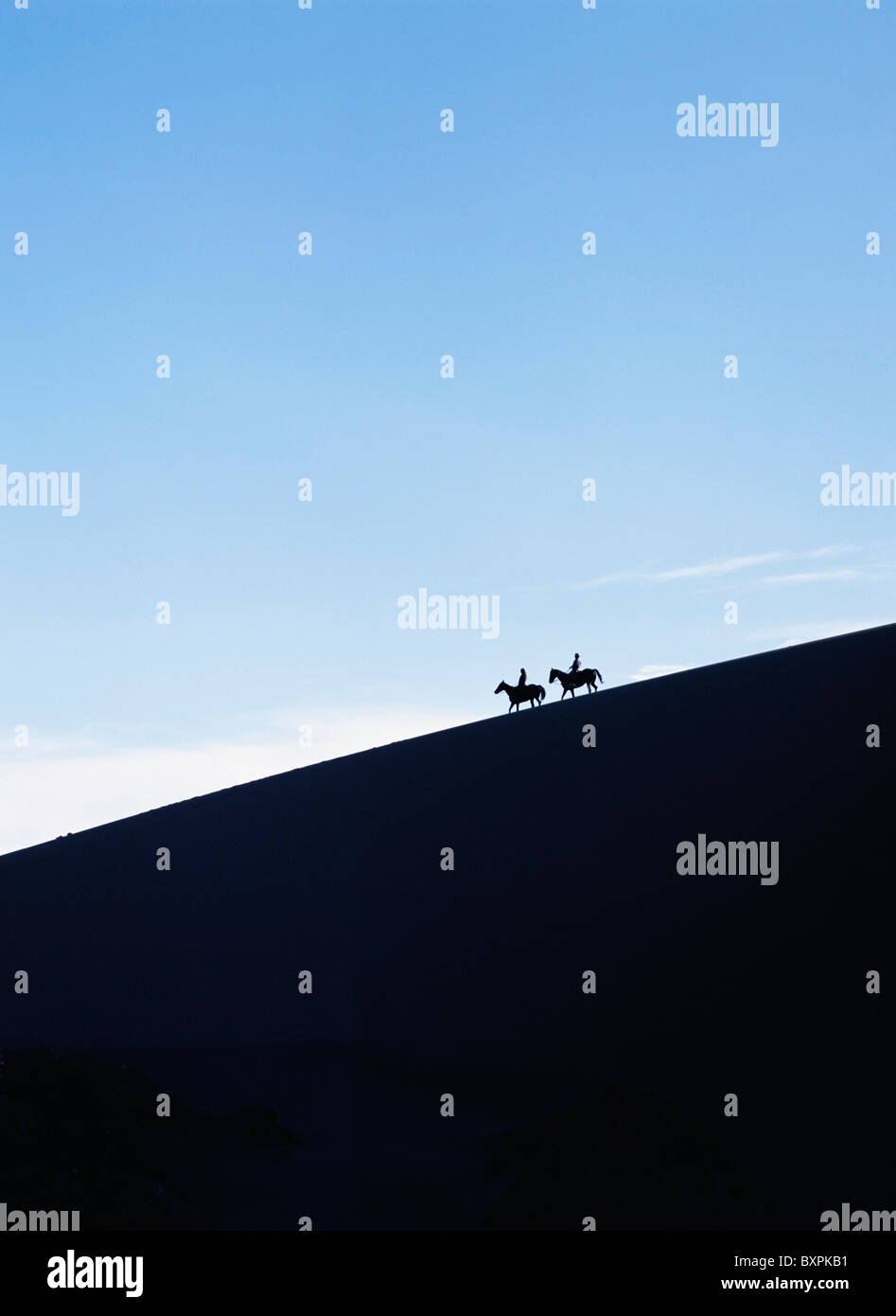 Silhouetted Horse Riders At Dusk On A Sand Dune In The Valle De La Muerte - Stock Image