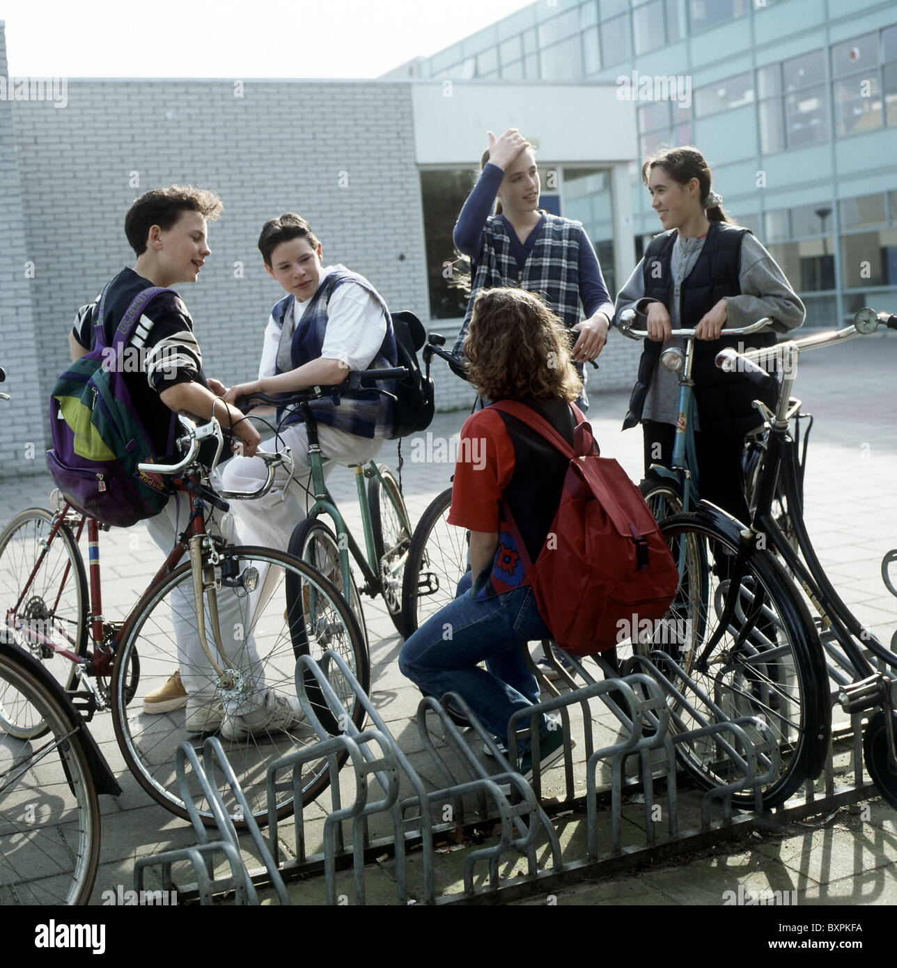 1980s - 1990s Youth : Teenagers on school yard chatting outside near bicycle parking rack after school time, on - Stock Image