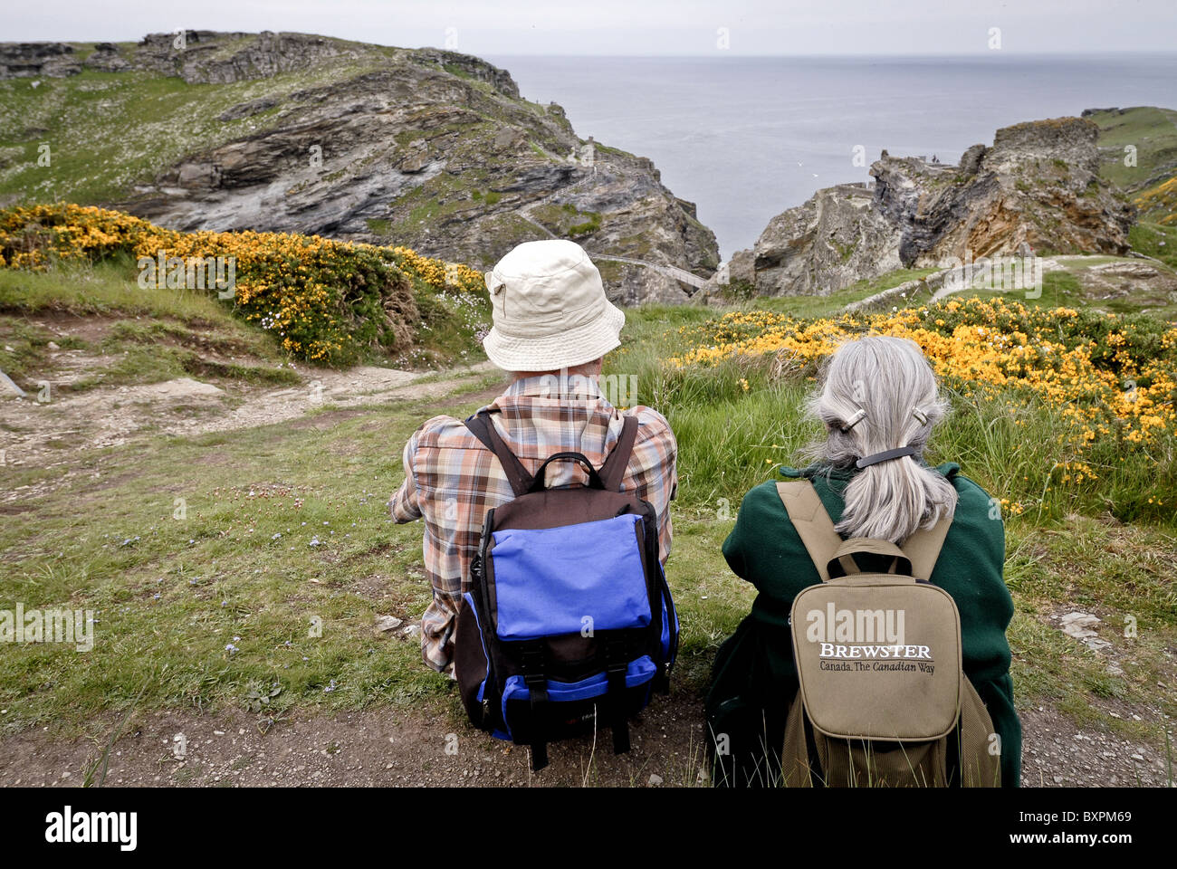 ELDERLY COUPLE OF RAMBLERS LOOKING OUT TO SEA, CORNWALL, - Stock Image
