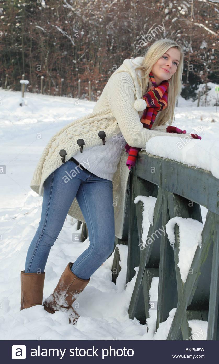 blond young woman enjoying a walk in winter landcsape - Stock Image