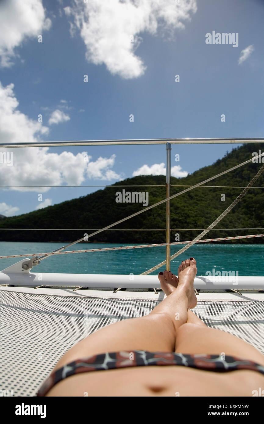 Sunbather In Bikini Sunbathing On Sailboat, Low Angle View - Stock Image