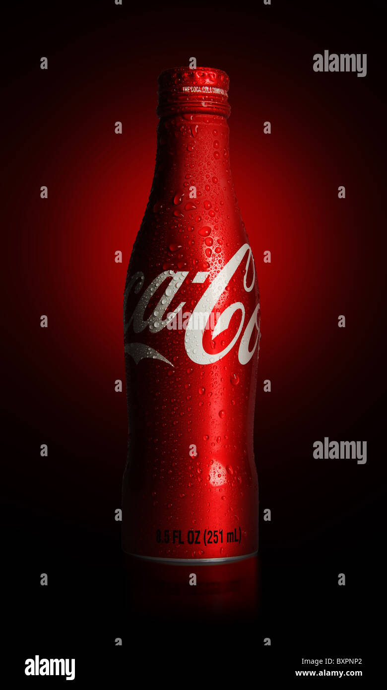 An 8.5 fluid ounce of Coca-Cola aluminum bottle with droplets shot on red and black radial background - Stock Image