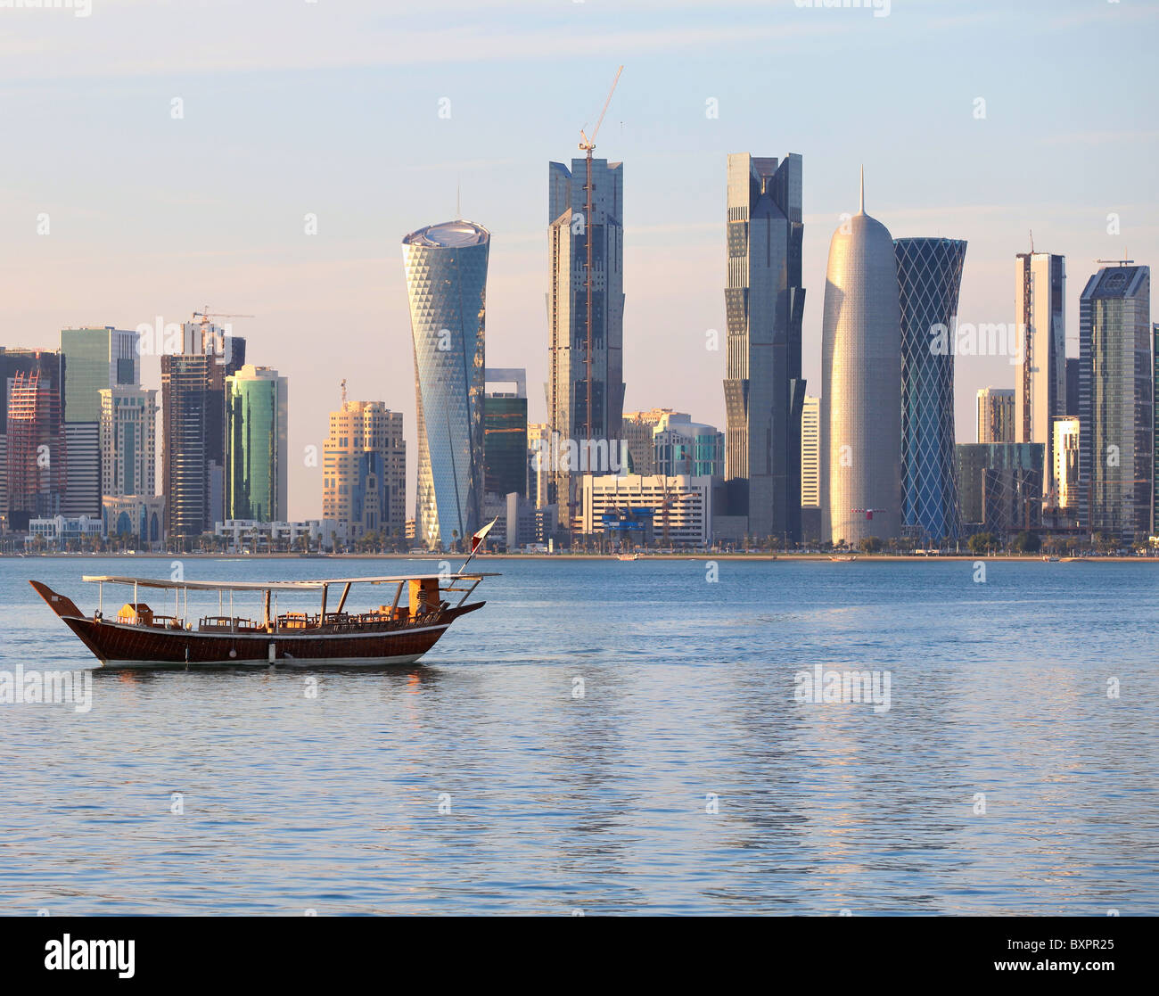 A dhow returns to harbour in Doha, Qatar, at sunset, with the city's modern skyline in the background. - Stock Image
