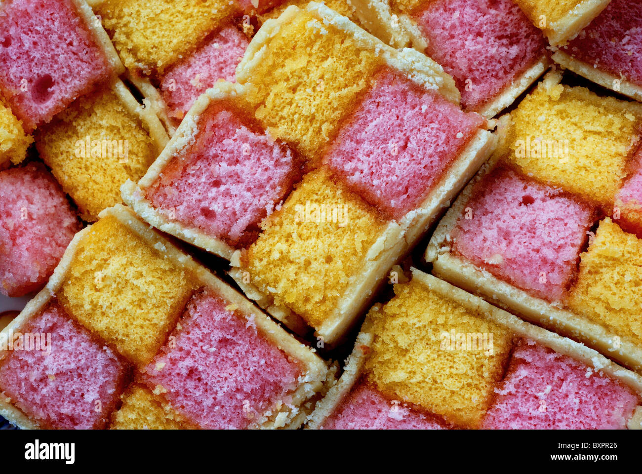 Slices of Battenburg cake,traditional English, filled with jam and with a marzipan icing - Stock Image