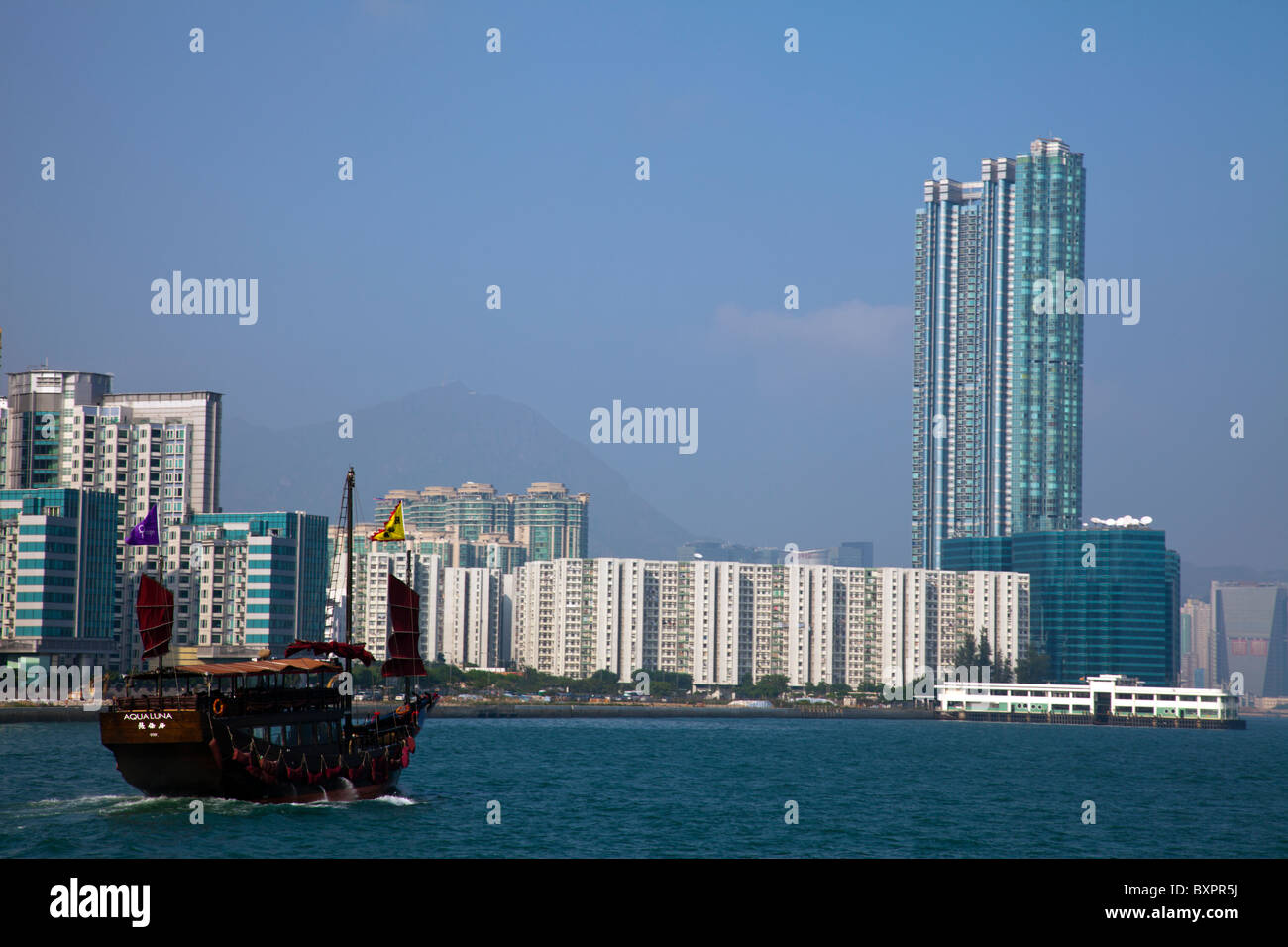 The iconic Chinese junk on Victoria Harbour against the Kowloon skyline, Hong Kong, China, Asia - Stock Image
