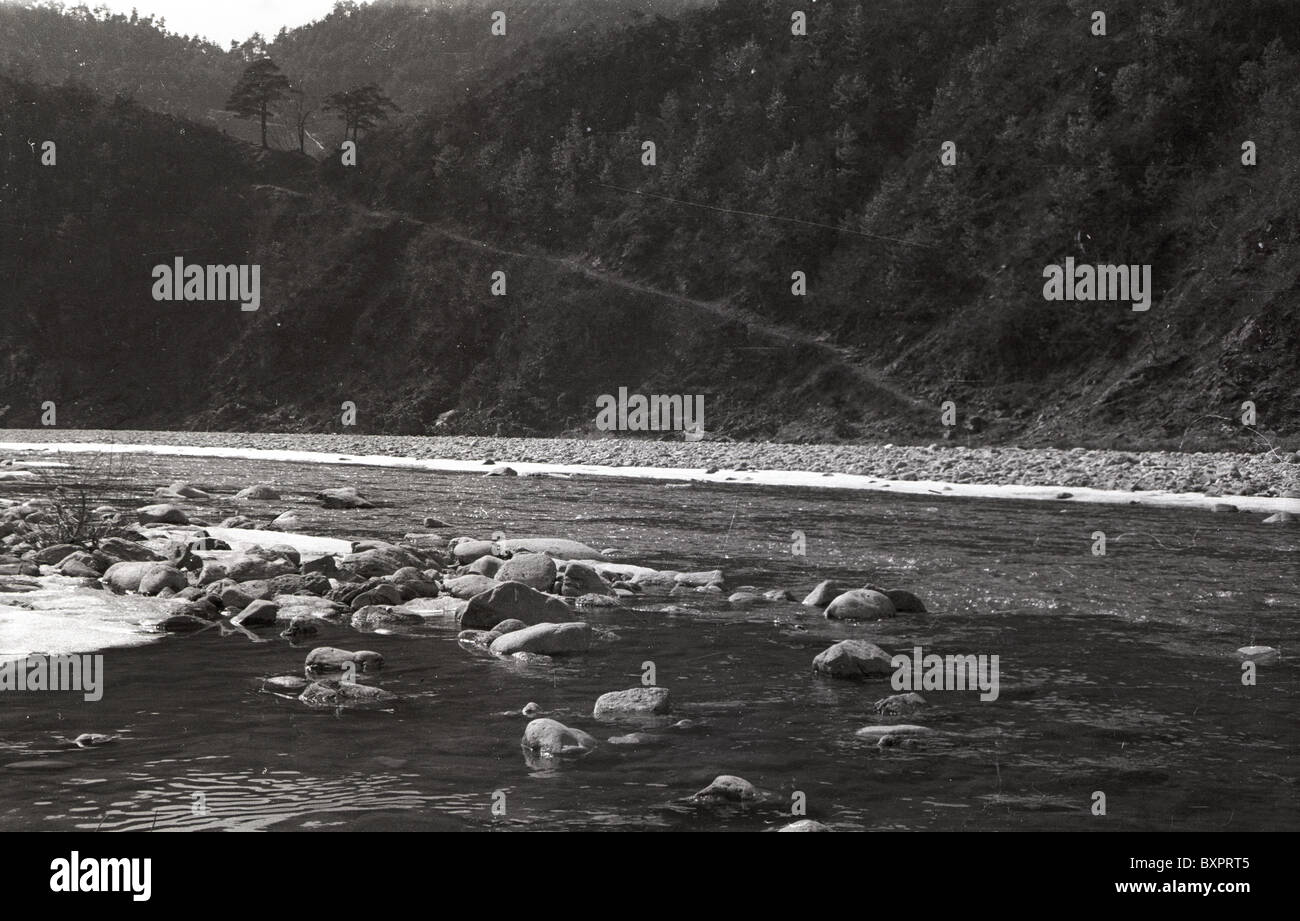 River running past tent of mash unit during korean war landscape black and white hill mountain trail day rocky water asia 1950s
