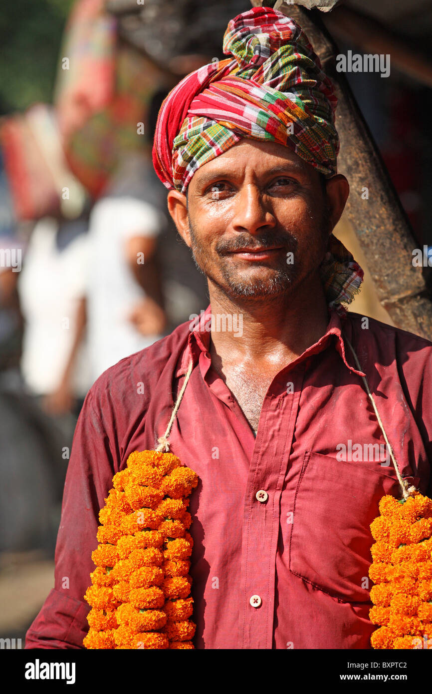 Indian man posing in street wearing garlands around neck - Stock Image