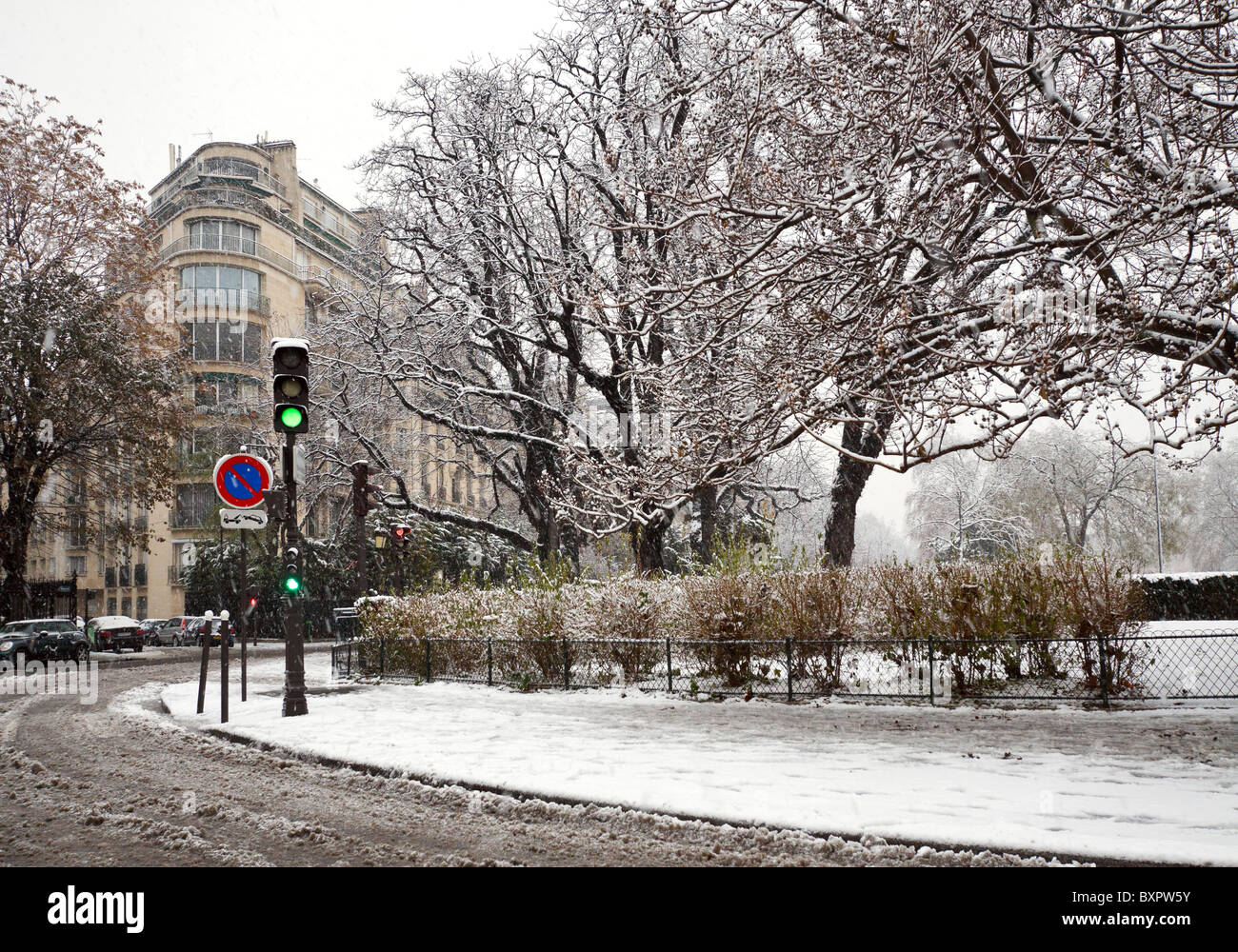 Snow covered trees and slushy streets in an early winter snowstorm in Paris, France - Stock Image