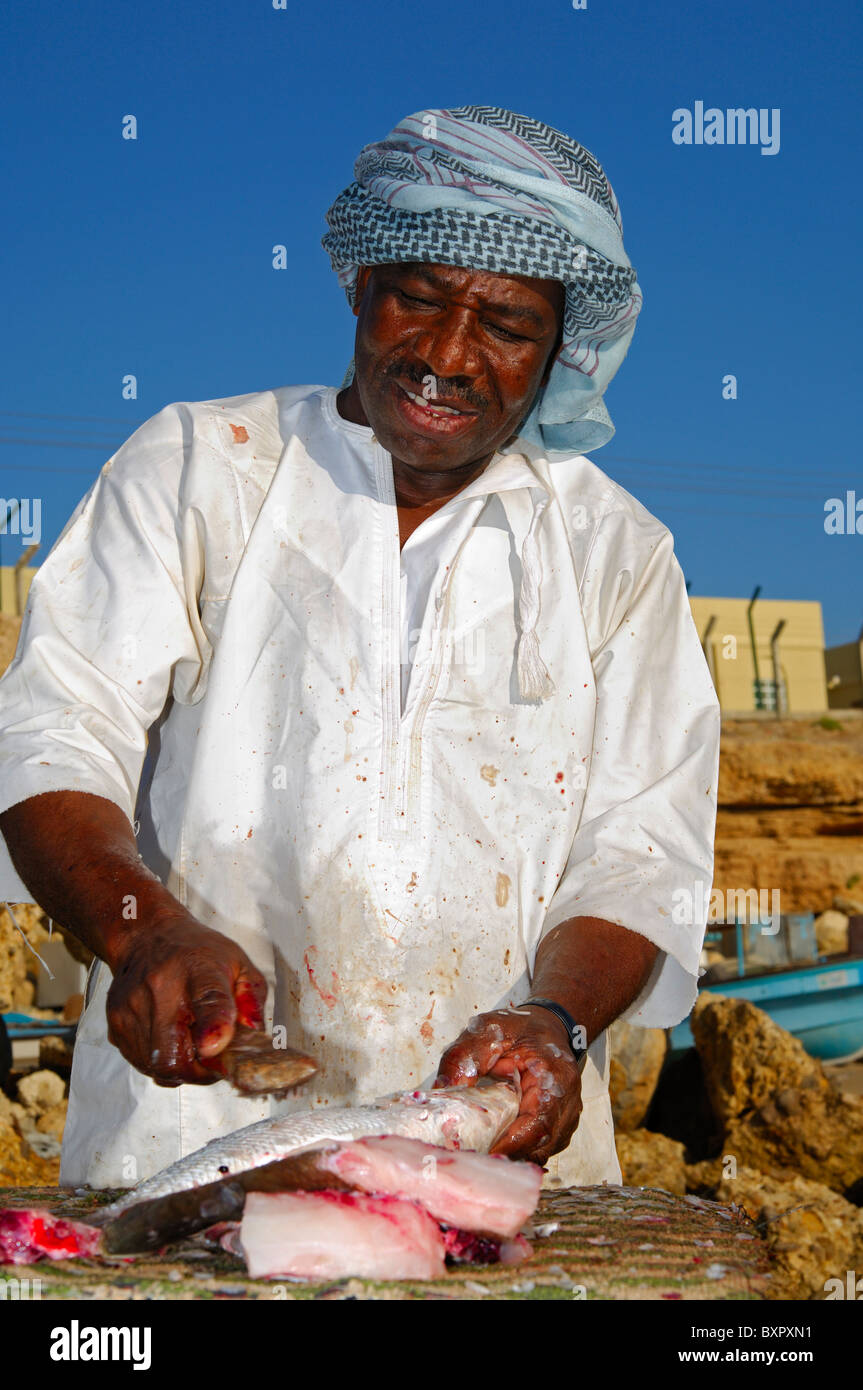 Dark-skinned fishmonger cutting fresh fish at an open-air market stall, Sur, Sultanate of Oman - Stock Image