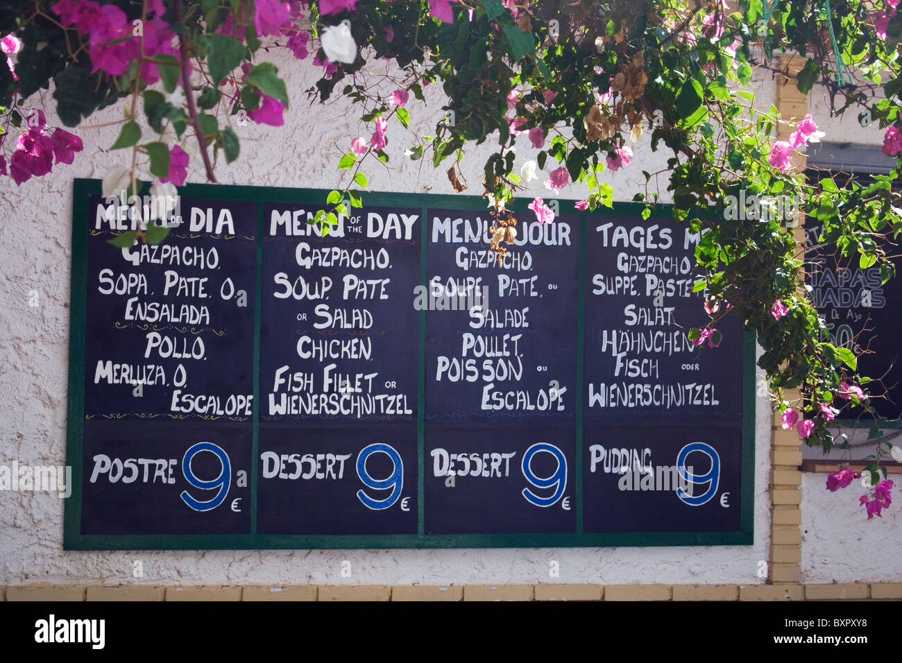 Menu board in four different languages advertising the menu of the day at nine euros. - Stock Image