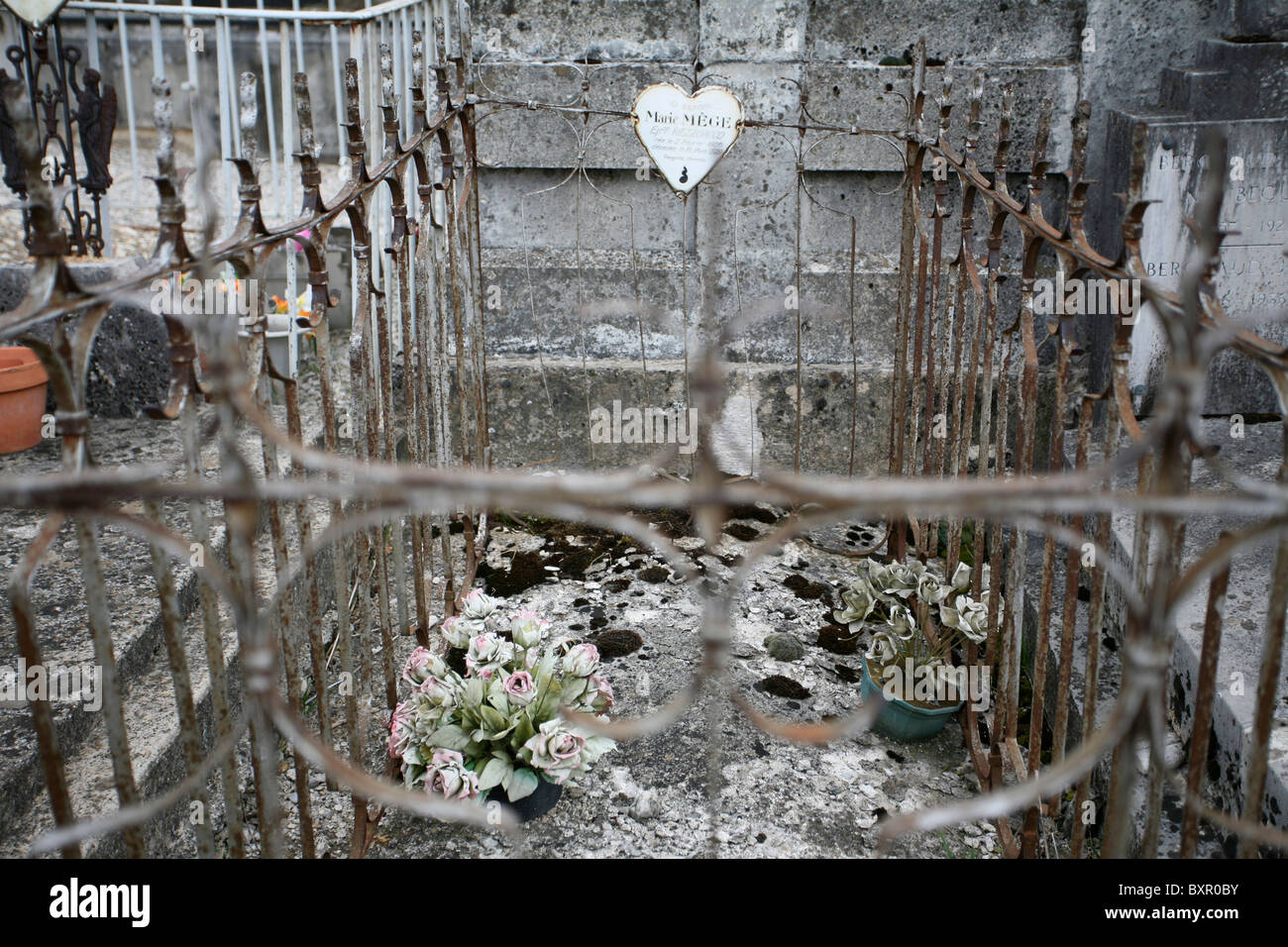 Old cemented tomb enclosed by decorative metal railings with heart nameplate & 2 weathered fake potted plants, - Stock Image