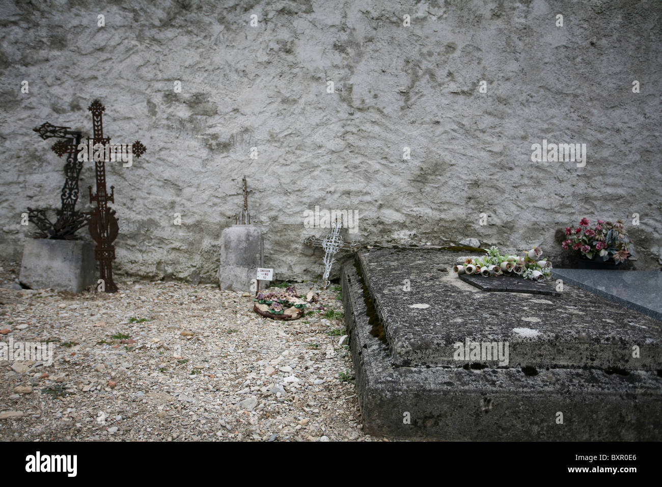 Grave sites with abandoned headstones and crosses leaning against a wall in Cimetière de Die, France - Stock Image