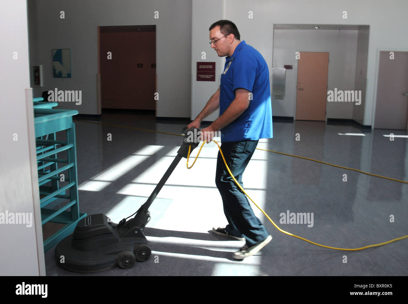A custodian buffs a floor. - Stock Image