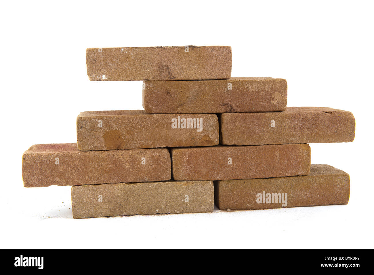 Building a wall with many bricks isolated over white - Stock Image