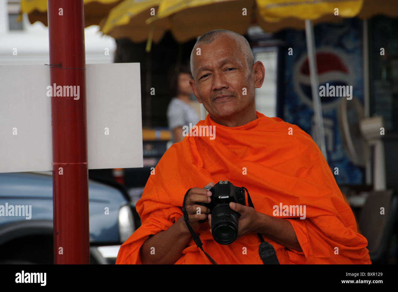 Old Buddhist Monk with Photocamera - Stock Image