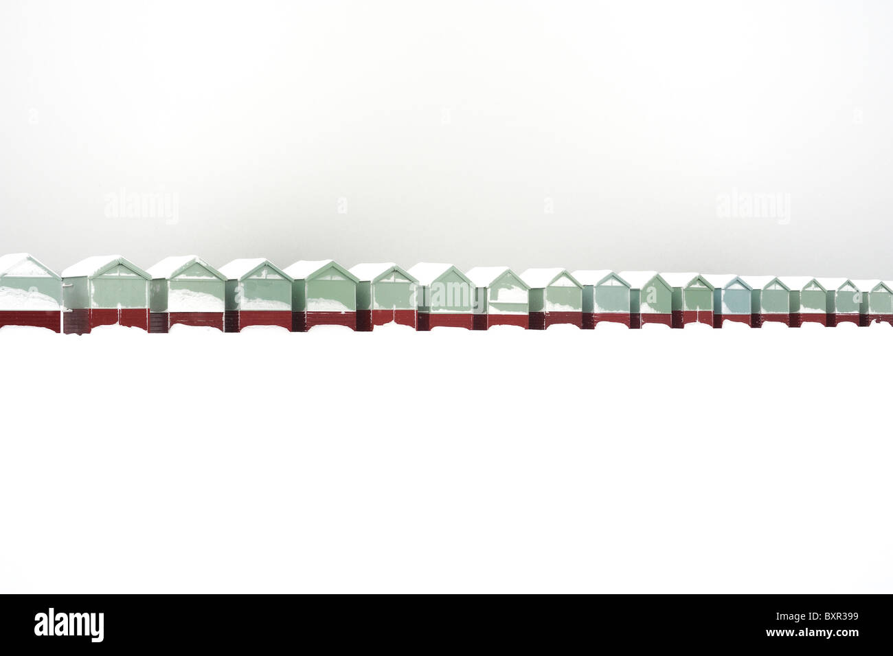 A row of beach huts covered in snow - Stock Image