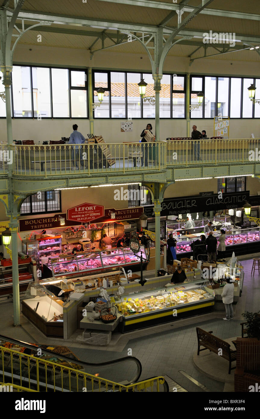 Diary & meat produce stalls in a French covered market shop an overview of trader and customer Town centre Les Sables Stock Photo