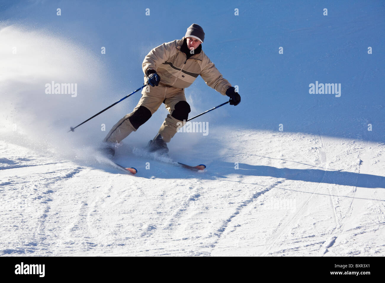 Man skier skiing fast downhill on snow ski slopes. Austria Europe. - Stock Image