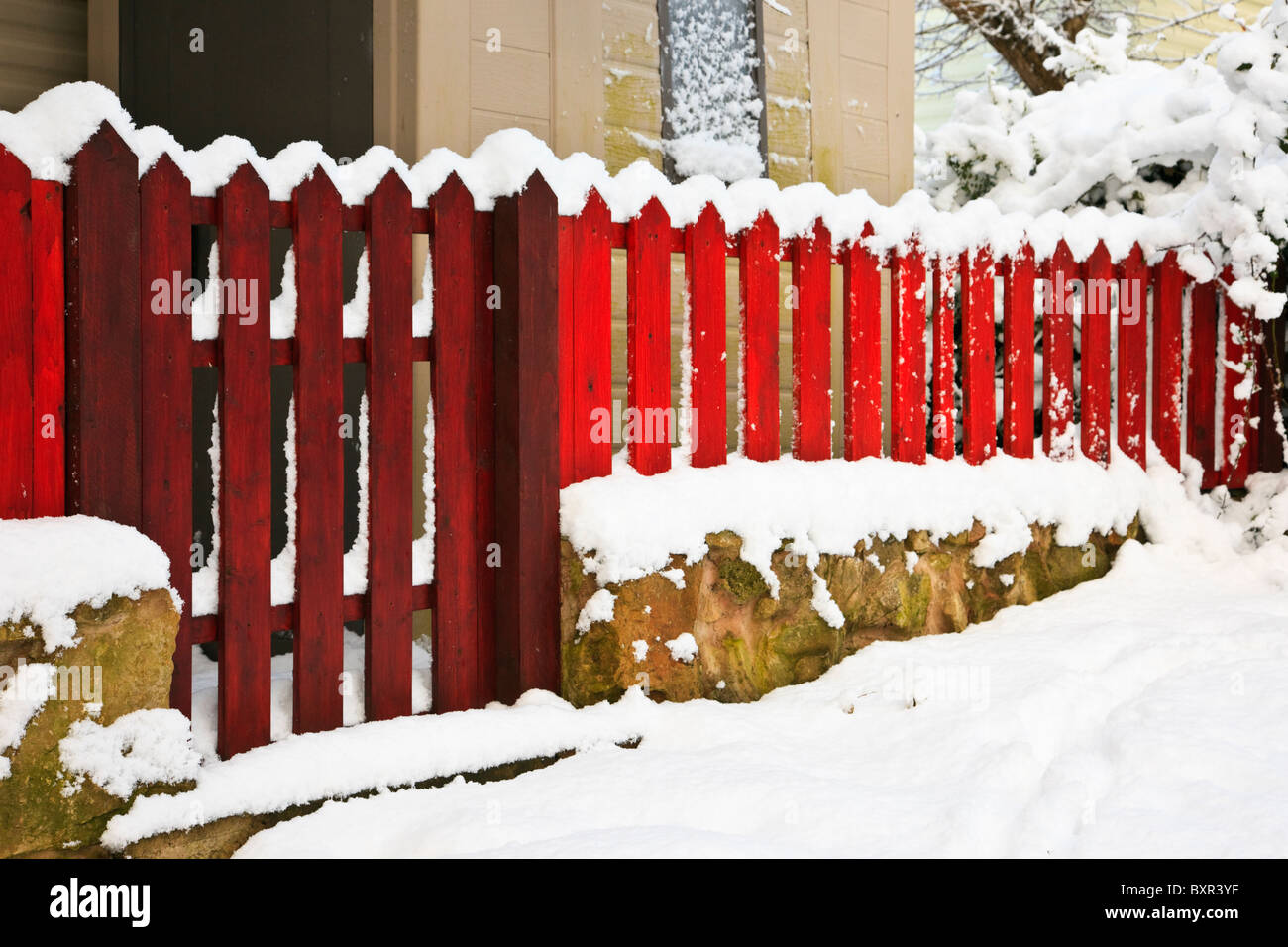 Red wooden picket fence and gate boundary around a domestic garden property in the snow. UK, Britain. - Stock Image