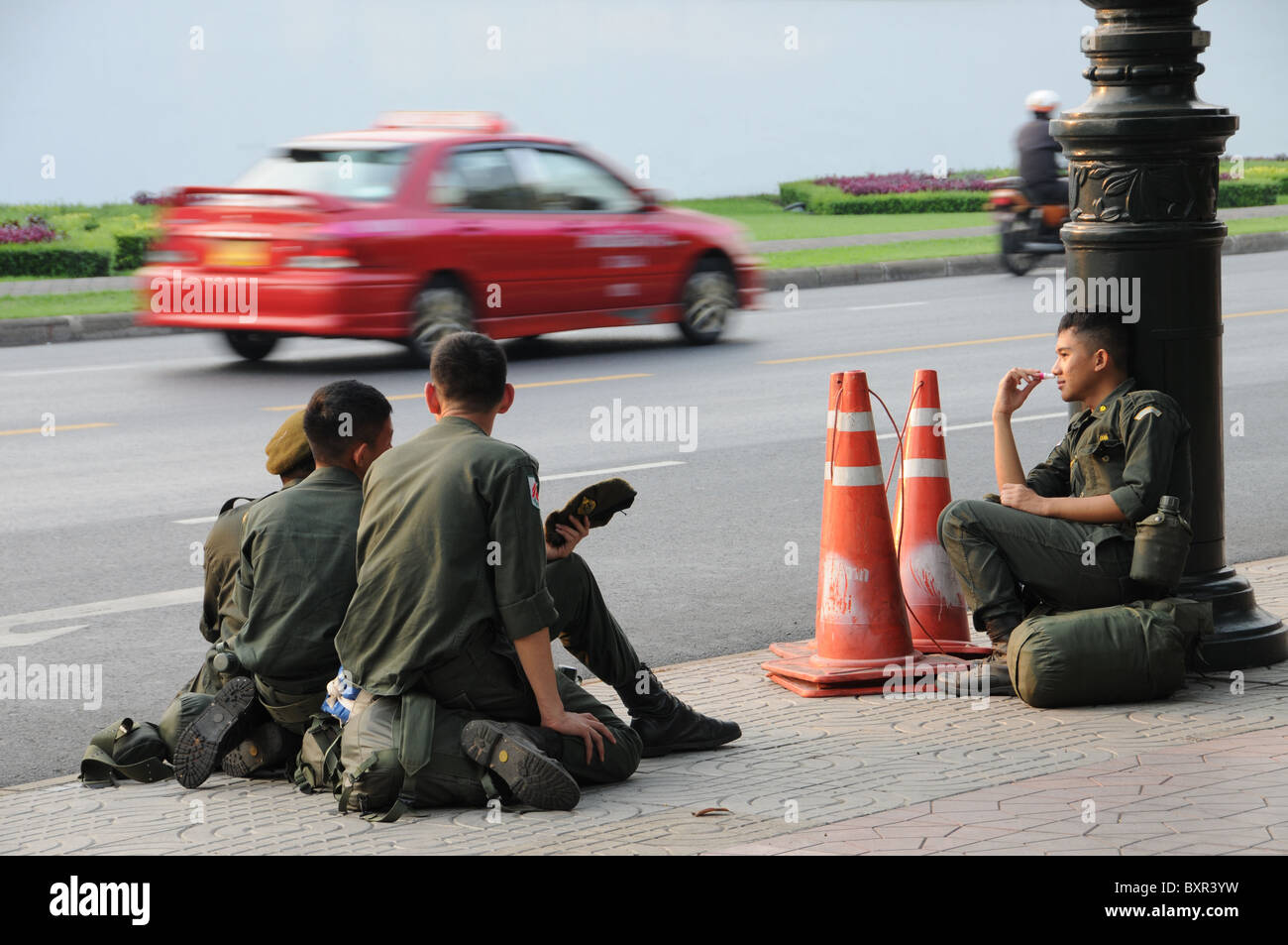 Young Soldiers waiting on a Street in Bangkok. - Stock Image