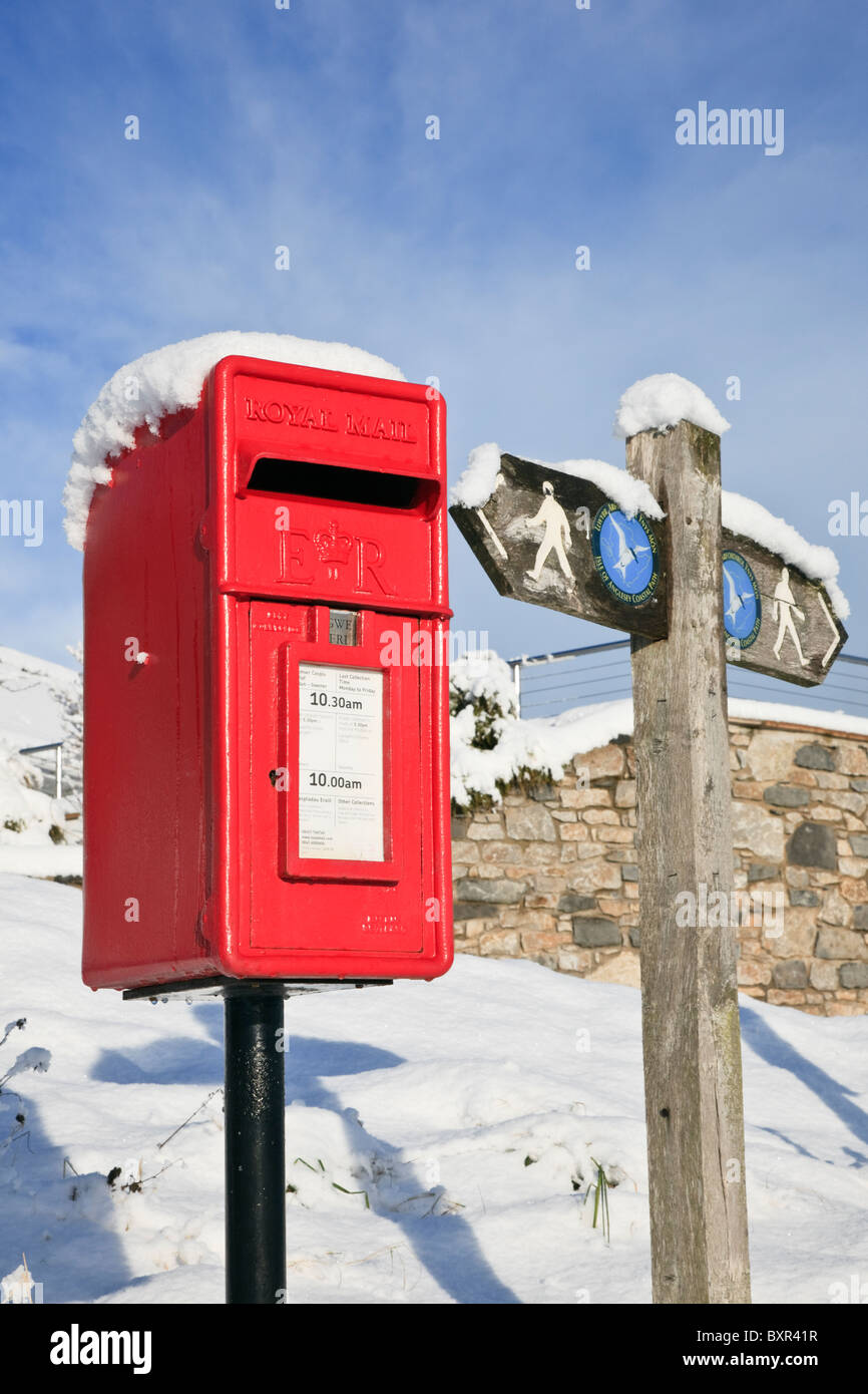 Traditional British red postbox and coastal path signpost in the snow. Isle of Anglesey, North Wales, UK, Britain - Stock Image
