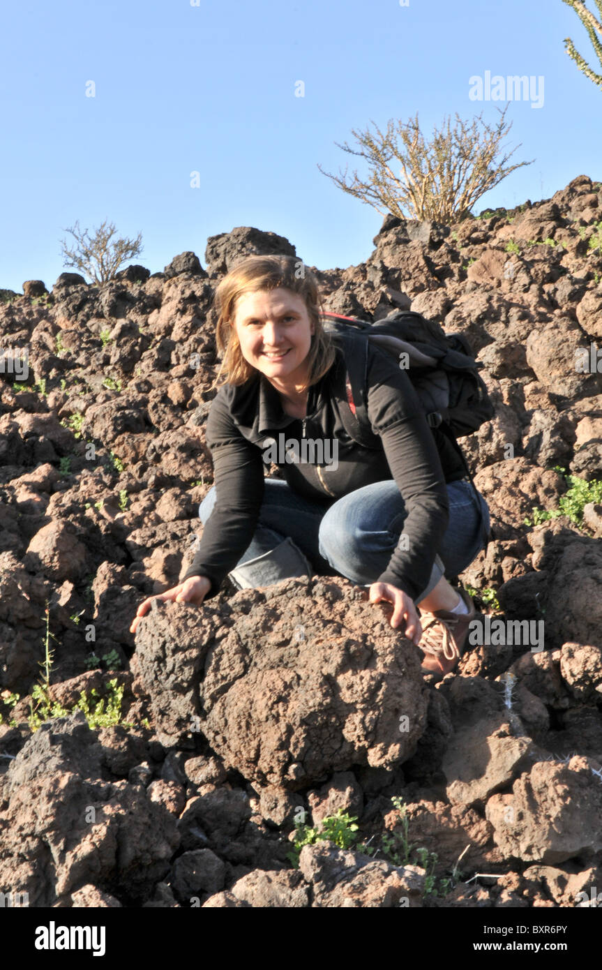 Woman showing volcanic bomb, ejected magma which cooled while falling, El Pinacate Biosphere Reserve, Sonora, Mexico - Stock Image
