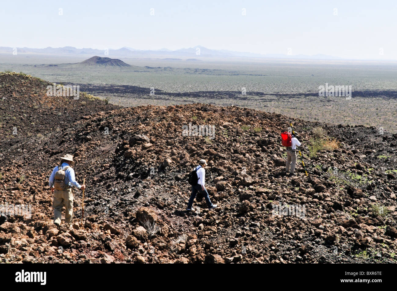 Hikers traversing rugged lava field on side of El Tecolote Cinder Cone, El Pinacate Biosphere Reserve, Sonora, Mexico - Stock Image