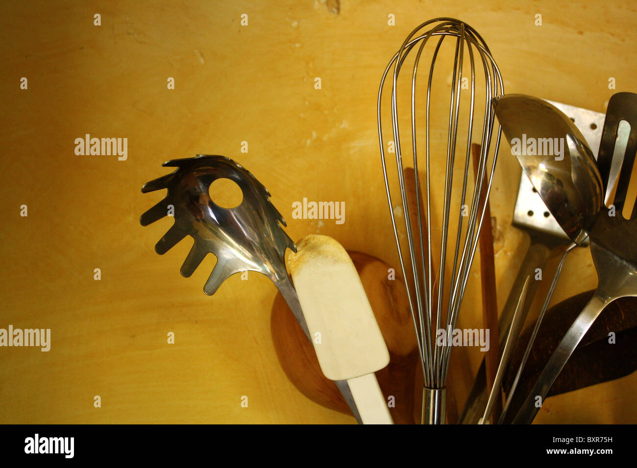 A Group Of Kitchen Utensils In A Pot Against A Yellow Kitchen Wall Stock Photo Alamy