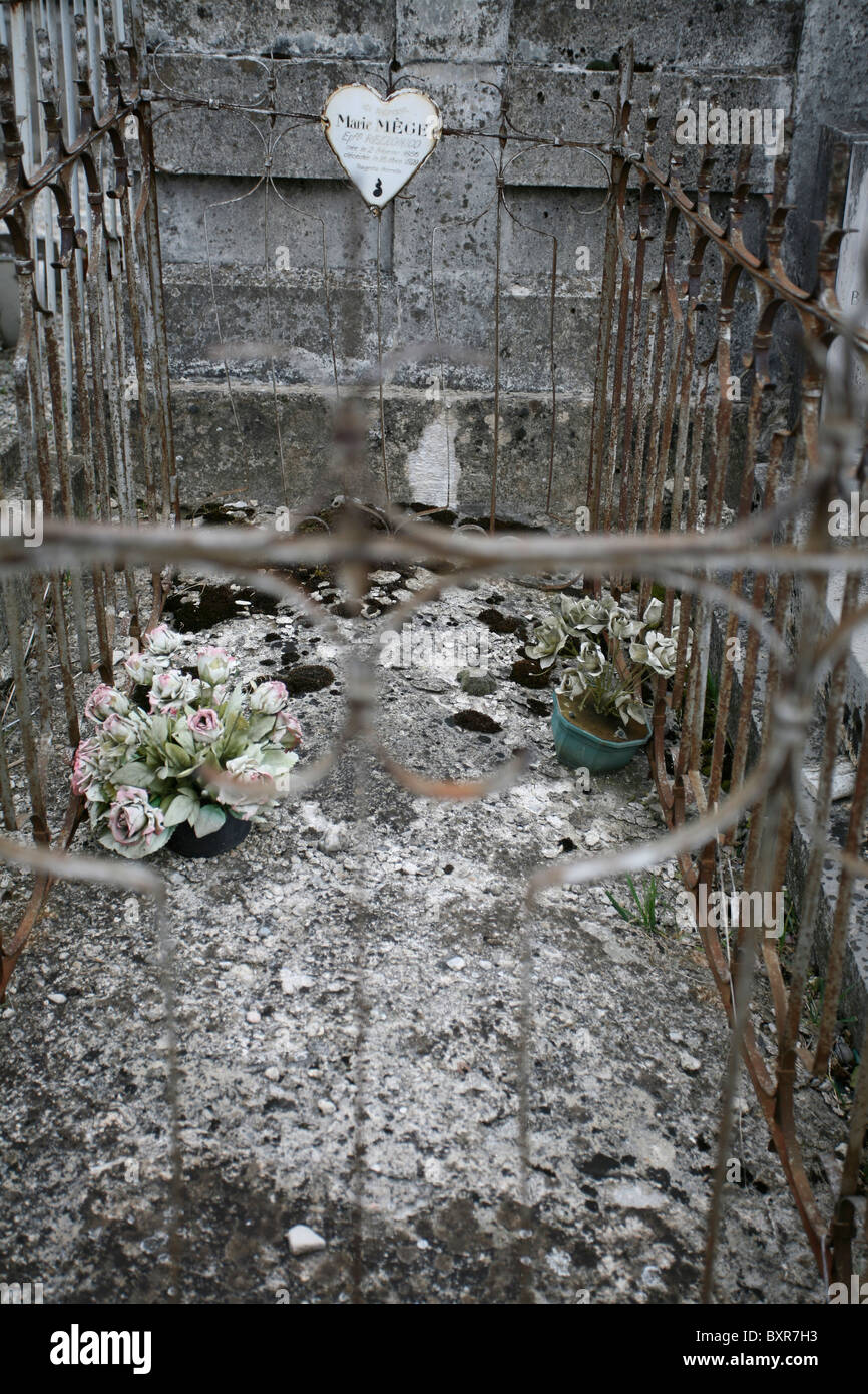 An old cemented tomb enclosed by decorative metal railings with heart shaped ornament and two weathered fake potted - Stock Image