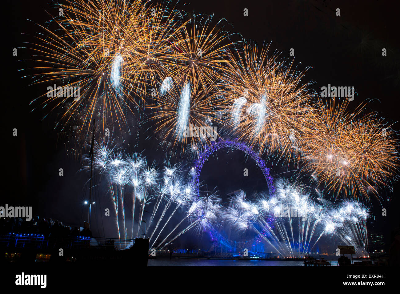 The London Eye lit up by fireworks on New Years eve 31st December 2010. - Stock Image