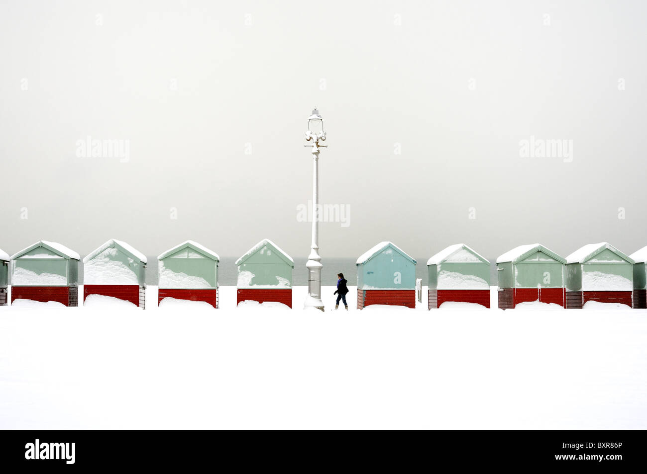 A walker passes a row of beach huts covered in snow - Stock Image