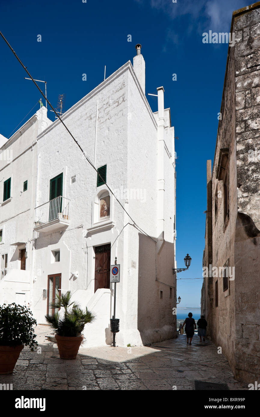 Alley between tall buildings in the old town of Ostuni, Puglia, Italy - Stock Image