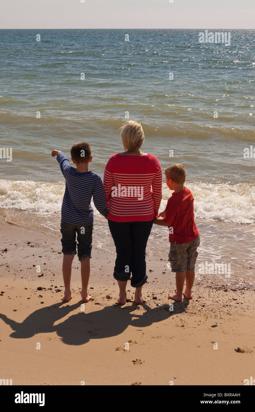 A MODEL RELEASED mother and two sons stand on a UK beach looking out to sea in the summer - Stock Image