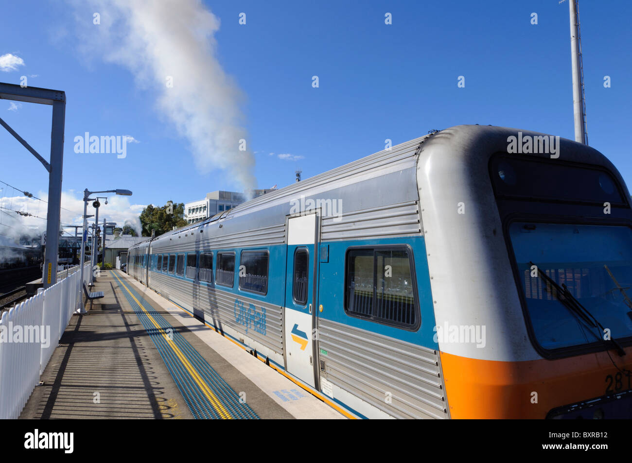 Diesel train producing a plume of smoke before departure from the station platform. Diesel multiple unit; emissions; - Stock Image