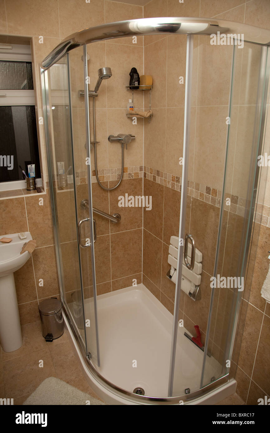 A disabled shower cubicle complete with chair and support handle bar in a residential property UK - Stock Image