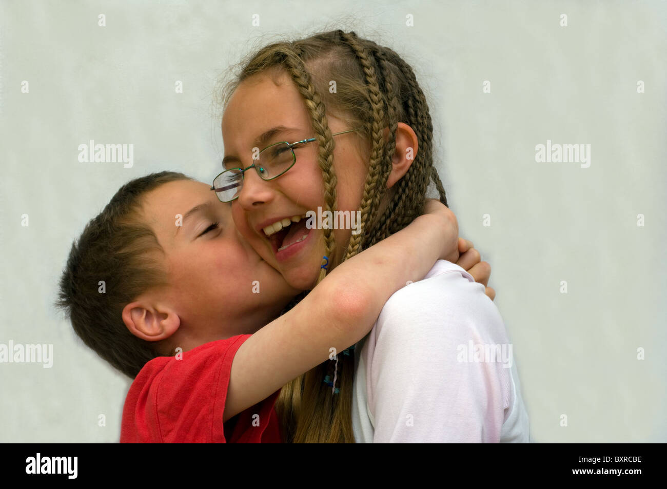 A younger brother kissing his older sister - Stock Image