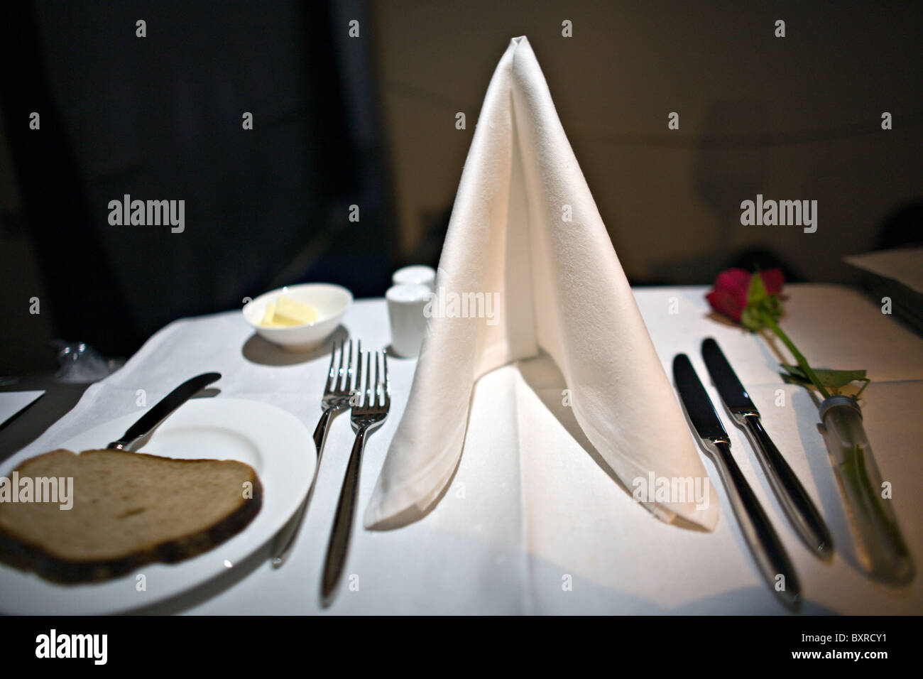 Lufthansa Airlines First Class meal setting with white linen, real silverware and a rose. - Stock Image