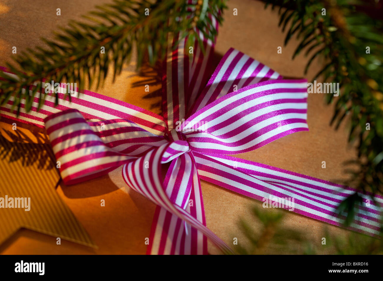Christmas present wrapped in brown paper and a stripy ribbon - Stock Image