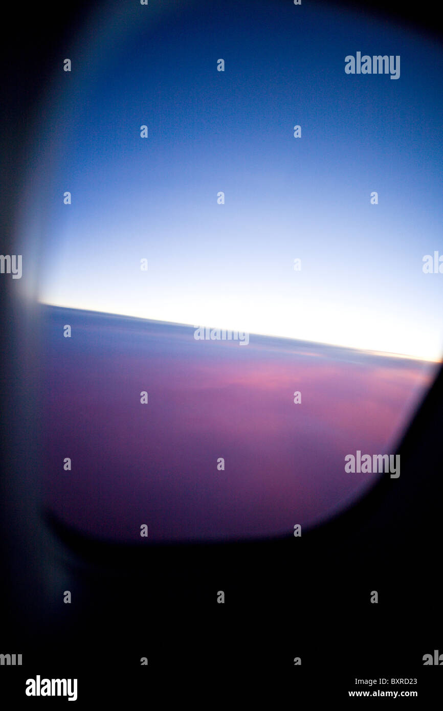 BEIJING, CHINA: Very abstract photo of a sunrise from an airplane window over Beijing, China. - Stock Image