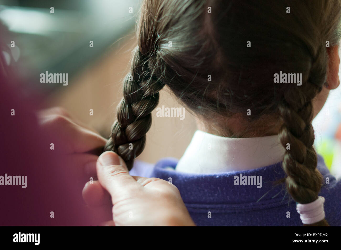 mother making plaits in child's hair - Stock Image