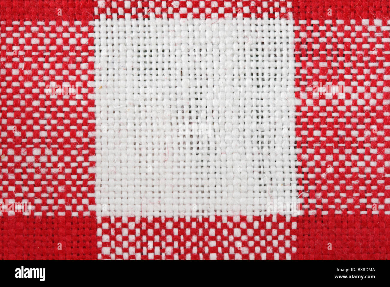 red and white tablecloth macro with a single white square and the surrounding red areas - Stock Image