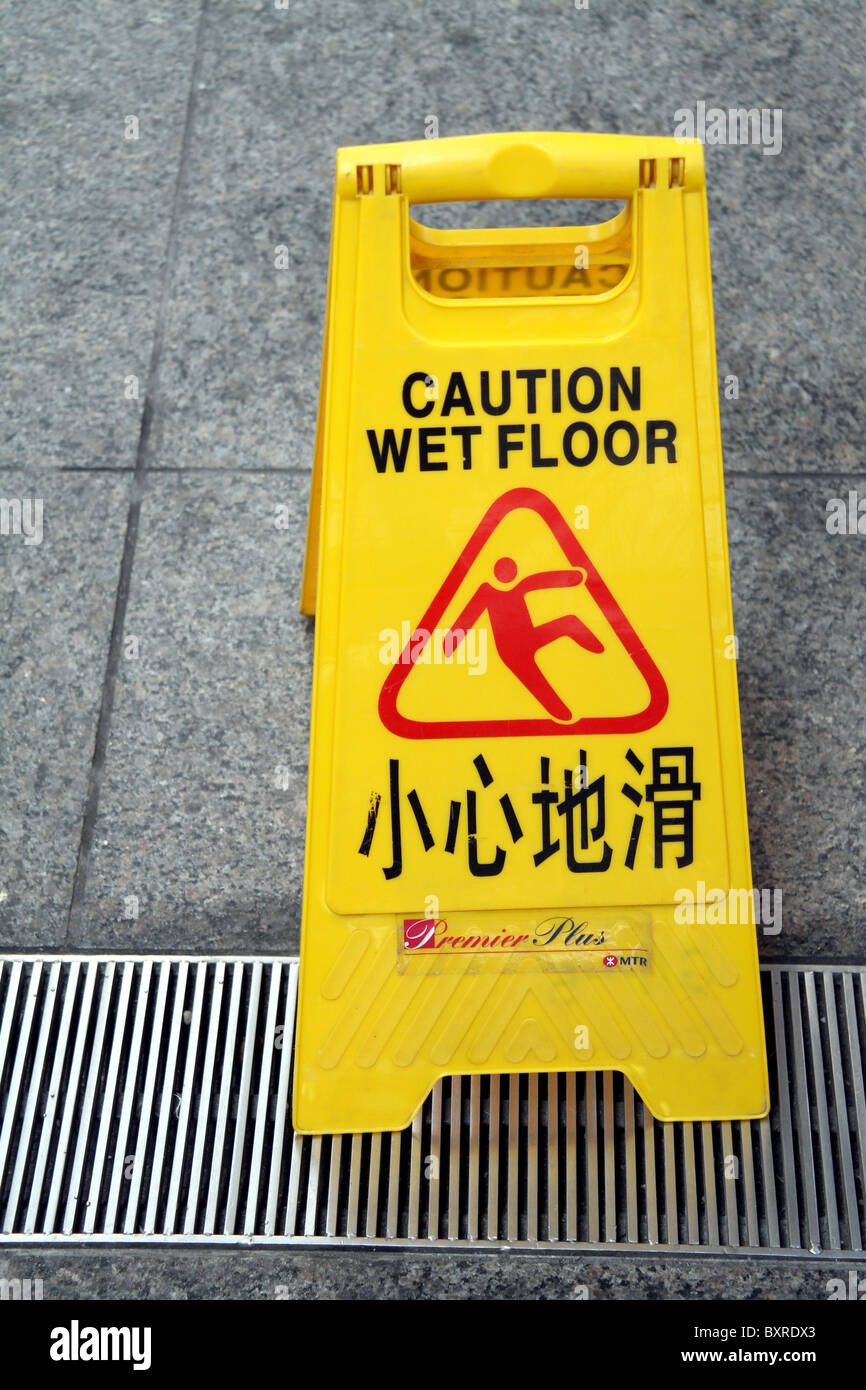 Chinese caution wet floor warning sign in Hong Kong, China - Stock Image