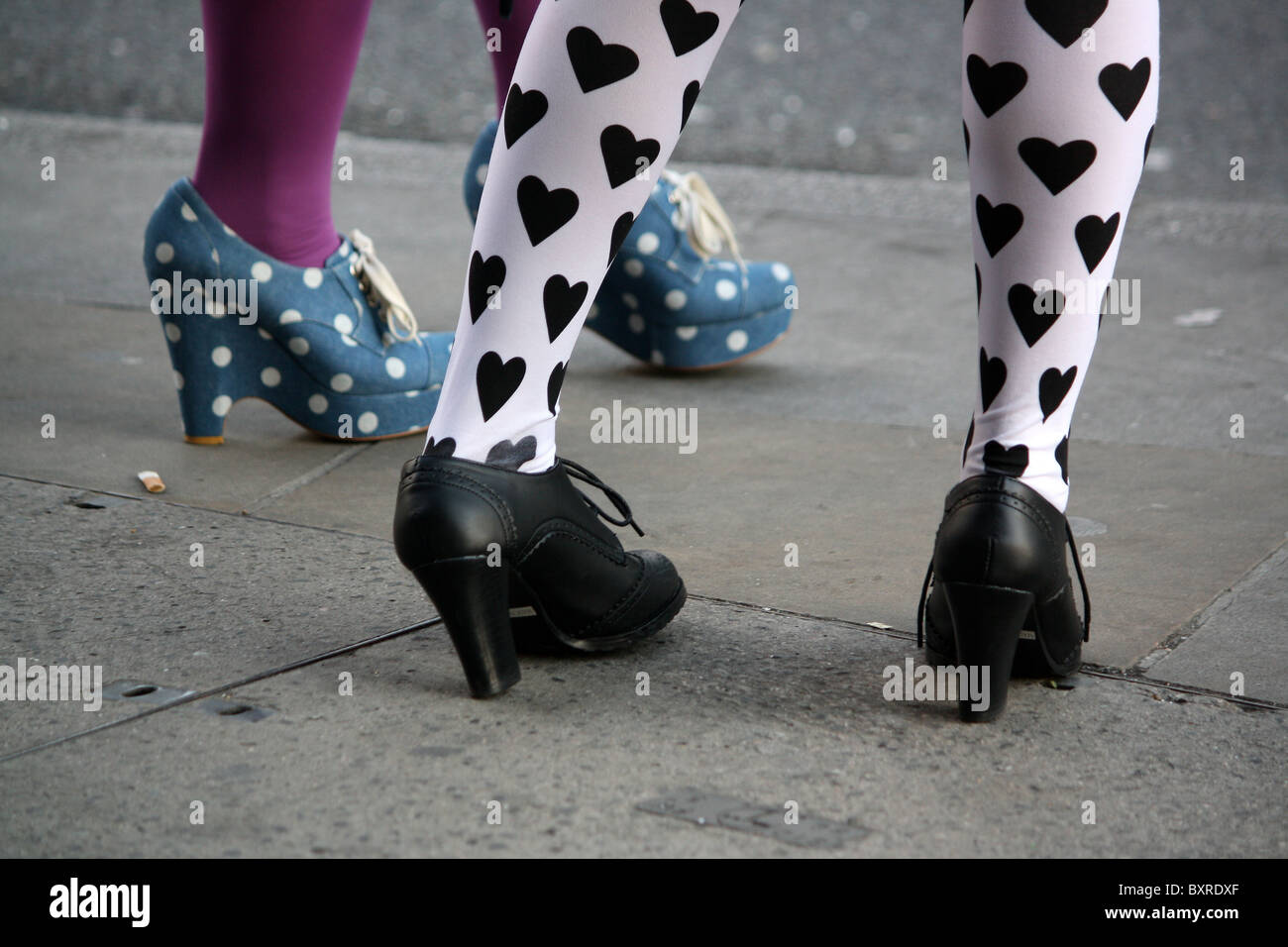 Cropped view of women standing on street wearing fashionable tights and rockabilly shoes - Stock Image