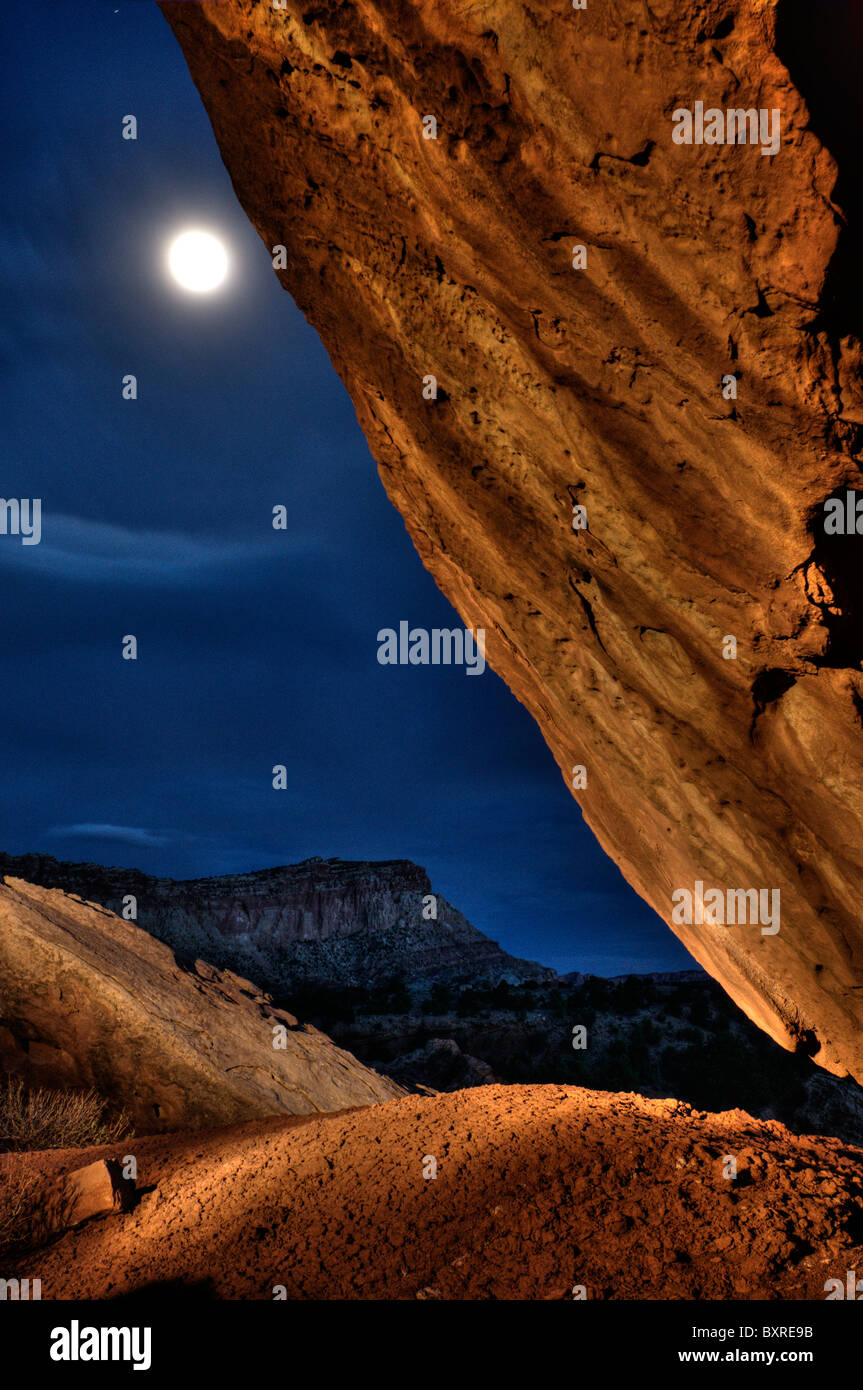 Surreal HDR image of light painting of rock and landscape with moon at Capitol Reef National Park - Stock Image