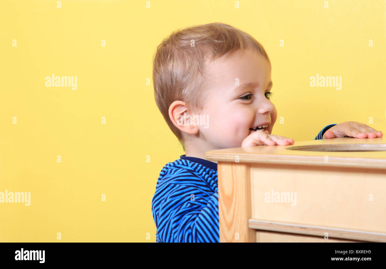 Cute european toddler having fun in kindergarten. Extra text space on left side. - Stock Image
