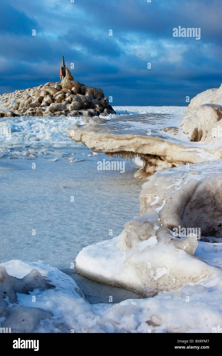 Ice flow surrounding a stone breakwater near the shore of Lake Erie in Madison Ohio USA - Stock Image