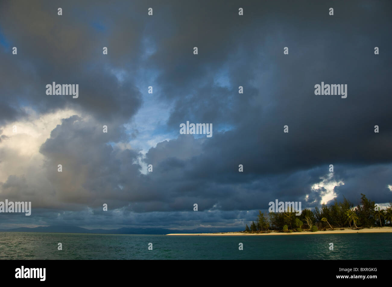 Rainclouds over island, view from boat, Island of Mantanani, South China Sea, East Malaysia. - Stock Image
